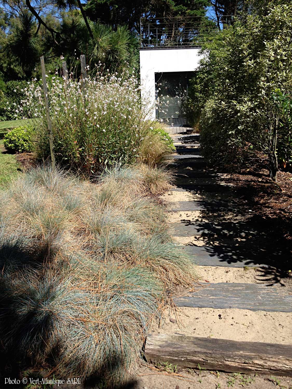 Aménagement de jardin avec pas japonais en dalles de schiste, massif de graminées, et Gauras lindheimeri
