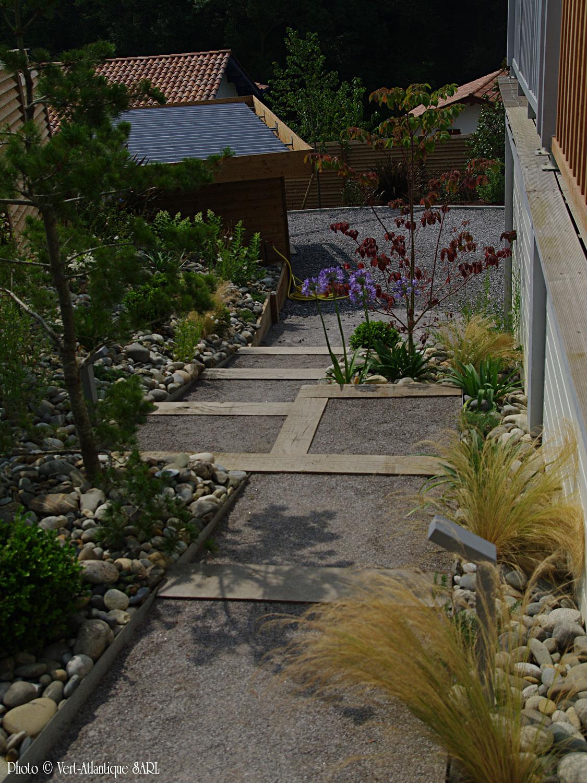 Aménagement entrée maison, avec escalier en traverses de chêne, arbustes divers et paillage en galets