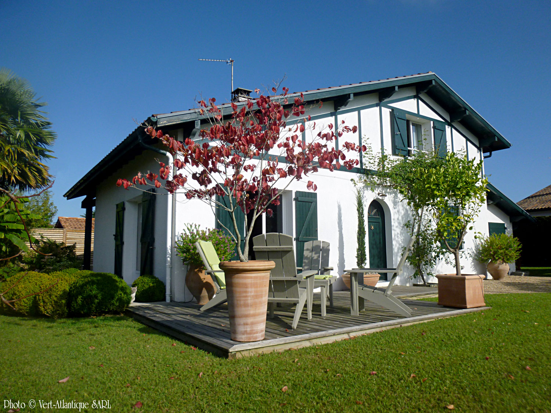 Aménagement jardin avec terrasse en bois et poteries, maison basque